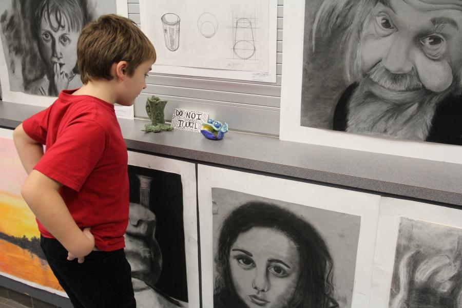 An amused child is tempted to rebel and touch displayed art.