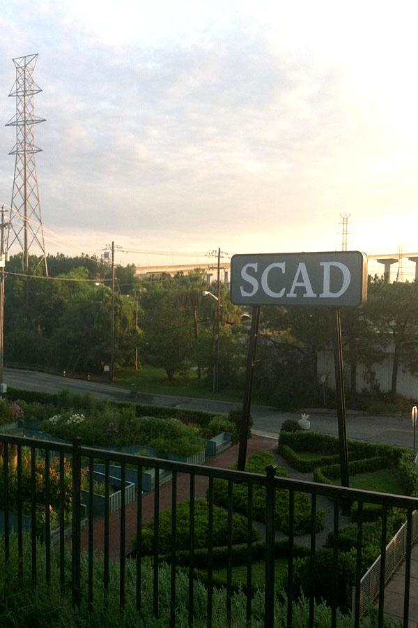A photo taken of the SCAD sign in the community garden from Turner House in Savannah Georgia at sunset.