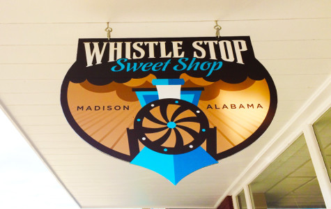 The Whistle Stop Sweet Shop sign that hangs outside of the store.