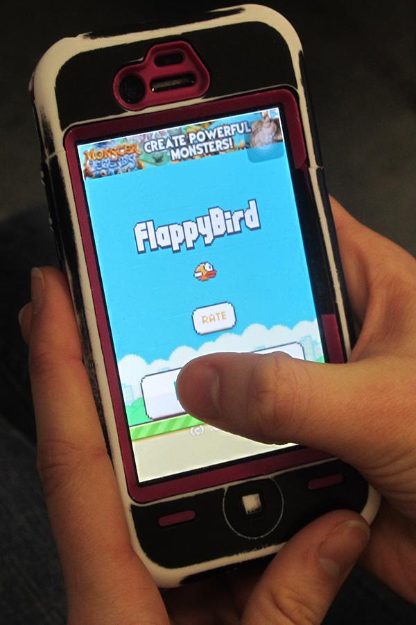 Student plays Flappy Bird app.