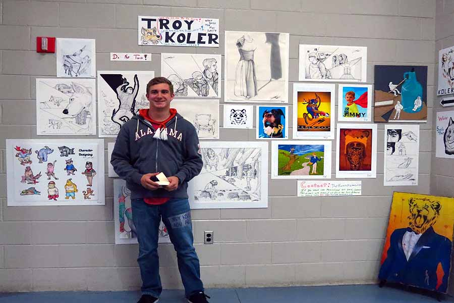 Troy Koler stands where his artwork covers the wall.