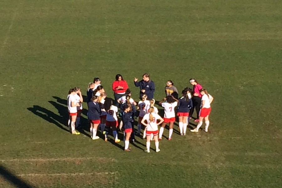 The girls' varsity soccer team meets at half-time to discuss tactics.
