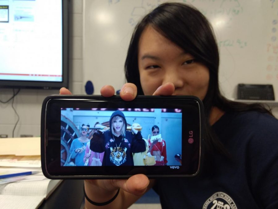 In the picture, Deborah Sheng is watching and reacting to Taylor Swift's music video for