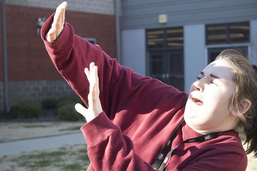 Junior Emilee Lamps attempts to shield her face from the blinding sun.